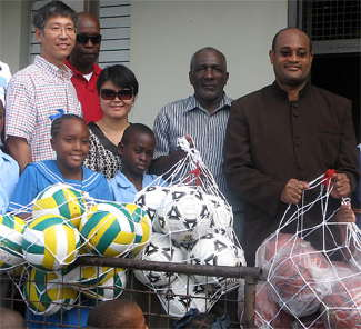 Government Minister Patrick Todd and students of Westbury School accept gifts from China's Ambassador: Footballs made in China's Laogai slave camps.